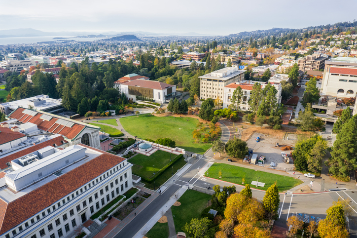 Aerial view of buildings in University of California, Berkeley campus on a sunny autumn day, view towards Richmond and the San Francisco bay shoreline in the background, California