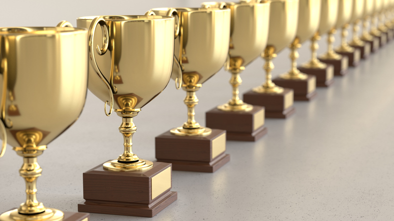 Line of Gold Trophys on a simple light surface. This image is a 3d render.