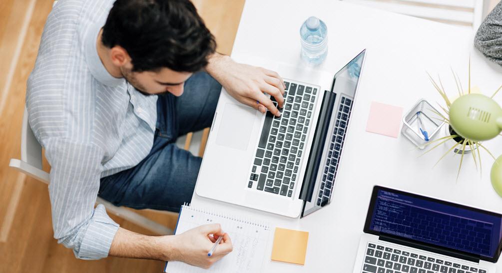 man sitting at laptop writing notes