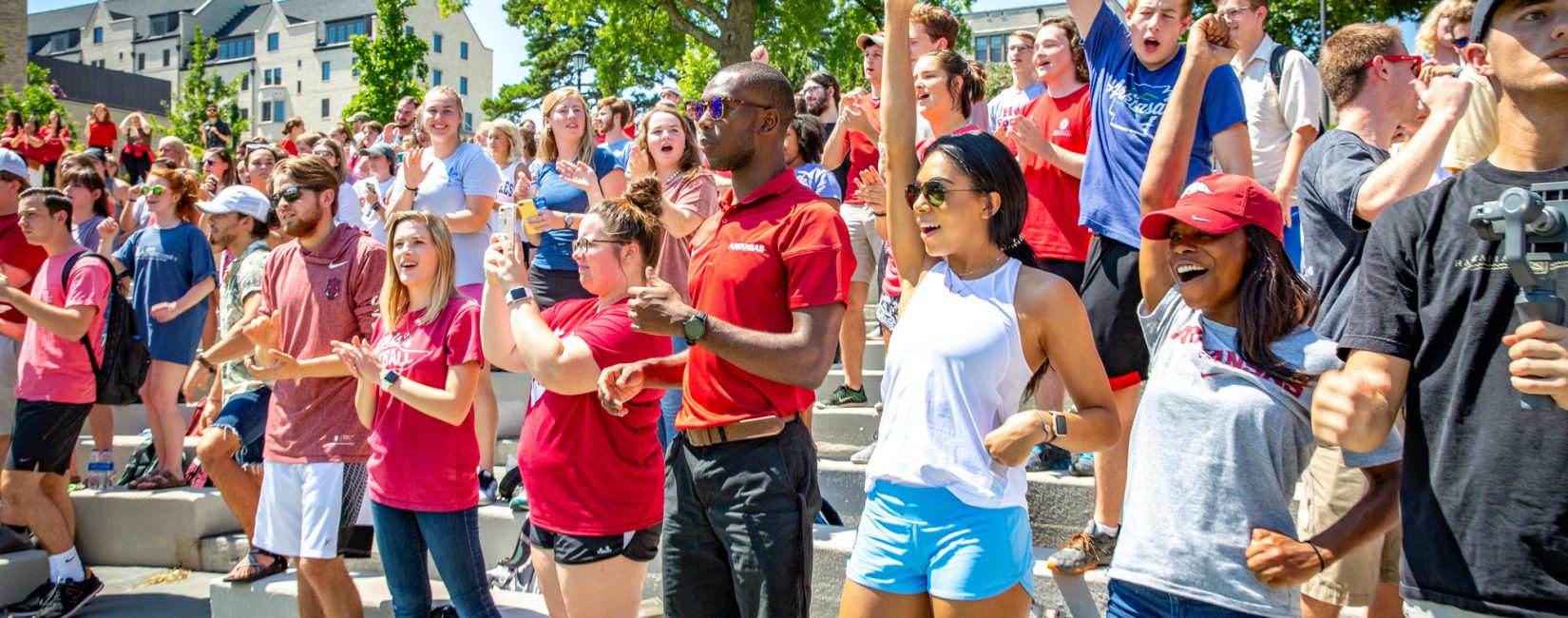 Colorful photo of students at One Hog Call event at Arkansas State University Greek Theater.