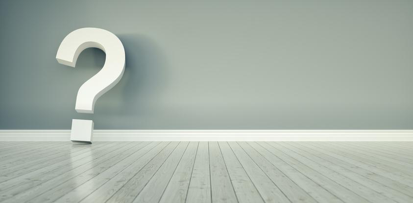 Question mark on hardwood floors against a wall