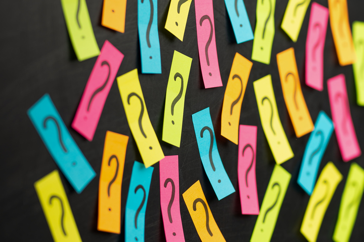 Question marks on post-it notes on blackboard