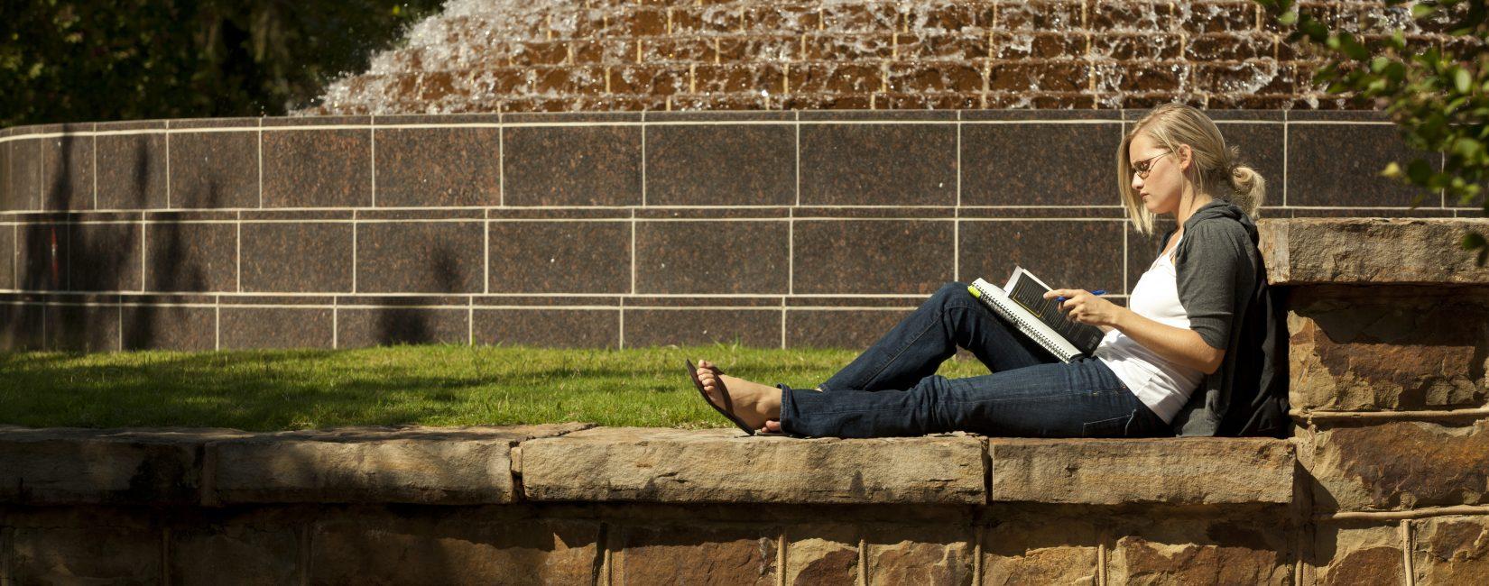 U of Arkansas student studying on rock wall.