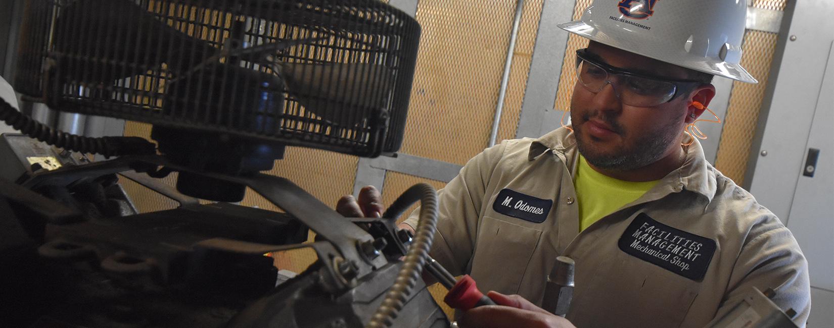 Worker at Auburn University working on equipment.