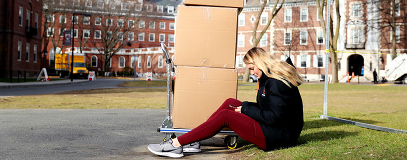 Student on phone sitting next to boxes.