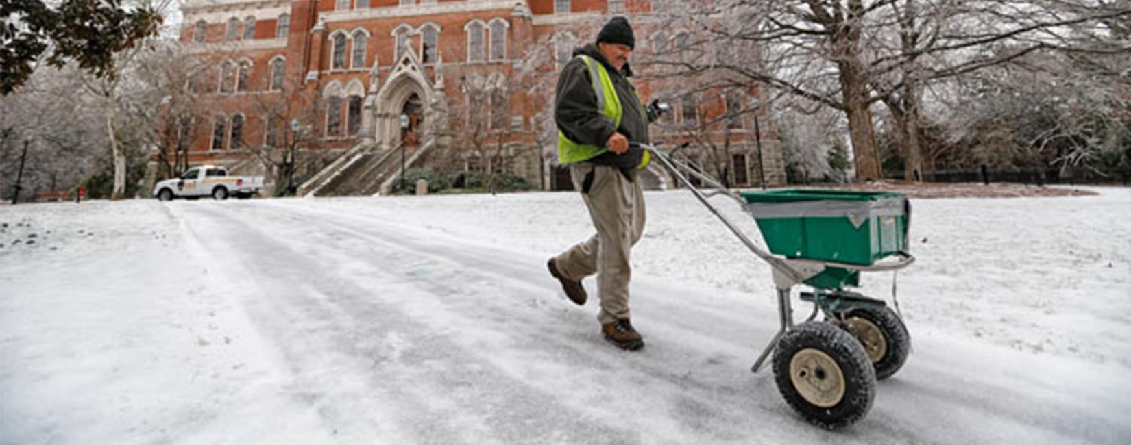 Vanderbilt University staff spreading salt on snow walkway.