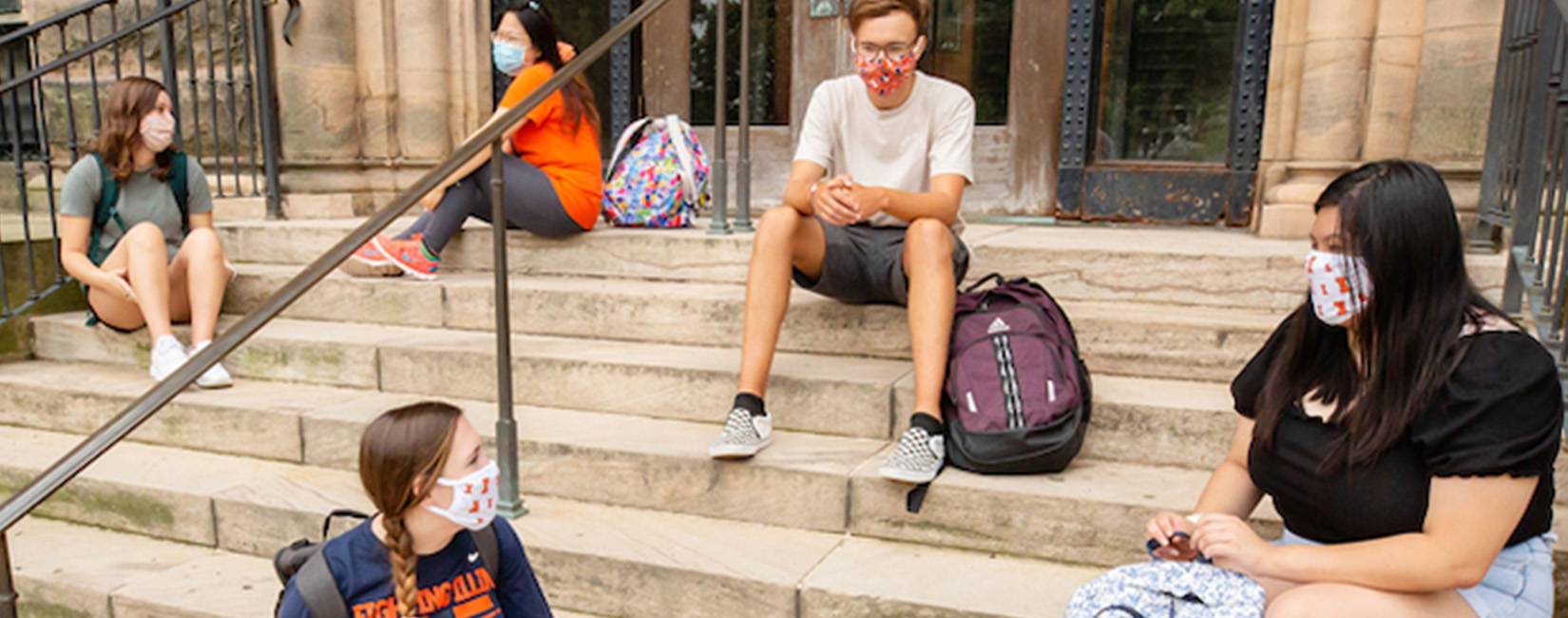 University of Illinois Urbana-Champaign students outside campus building sitting on steps.Cropped